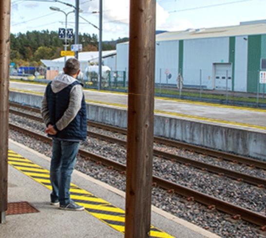 Persona esperando en un andén al aiire libre sobre una señal podotactil que marca la zona de peligro